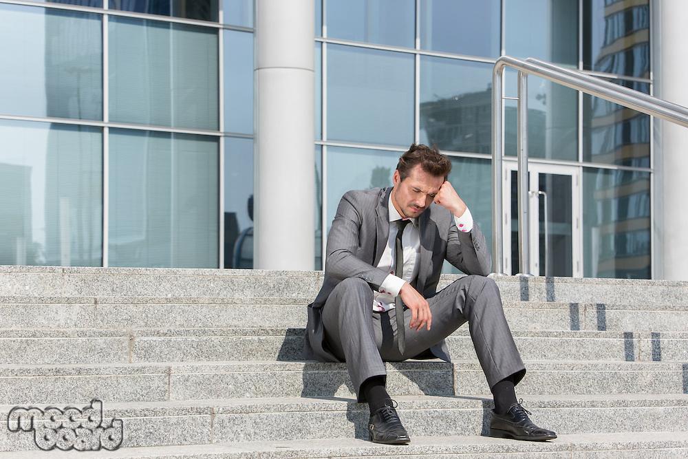 Full length of stressed businessman sitting on steps outside office