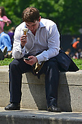 © Licensed to London News Pictures. 31/05/2013. London, UK A man checks his phone whilst eating an ice-cream. Children and office workers enjoy the hot weather near to City Hall and Tower Bridge in London today May 31st 2013. Photo credit : Stephen Simpson/LNP