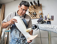 Mature male worker buffing prosthetic limb