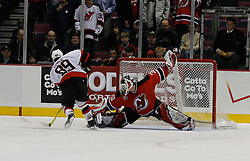 Apr 3, 2007; East Rutherford, NJ, USA; New Jersey Devils goalie Martin Brodeur (30) makes a save on Ottawa Senators center Mike Comrie (89) during the overtime shootout at Continental Airlines Arena in East Rutherford, NJ.
