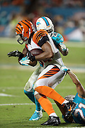 Cincinnati Bengals tight end Jermaine Gresham (84) gets hit by Miami Dolphins free safety Reshad Jones (20) and Miami Dolphins cornerback Brent Grimes (21) but gets a first down on a pass reception and run in overtime during the NFL week 9 football game against the Miami Dolphins on Thursday, Oct. 31, 2013 in Miami Gardens, Fla.. The Dolphins won the game 22-20 in overtime. ©Paul Anthony Spinelli