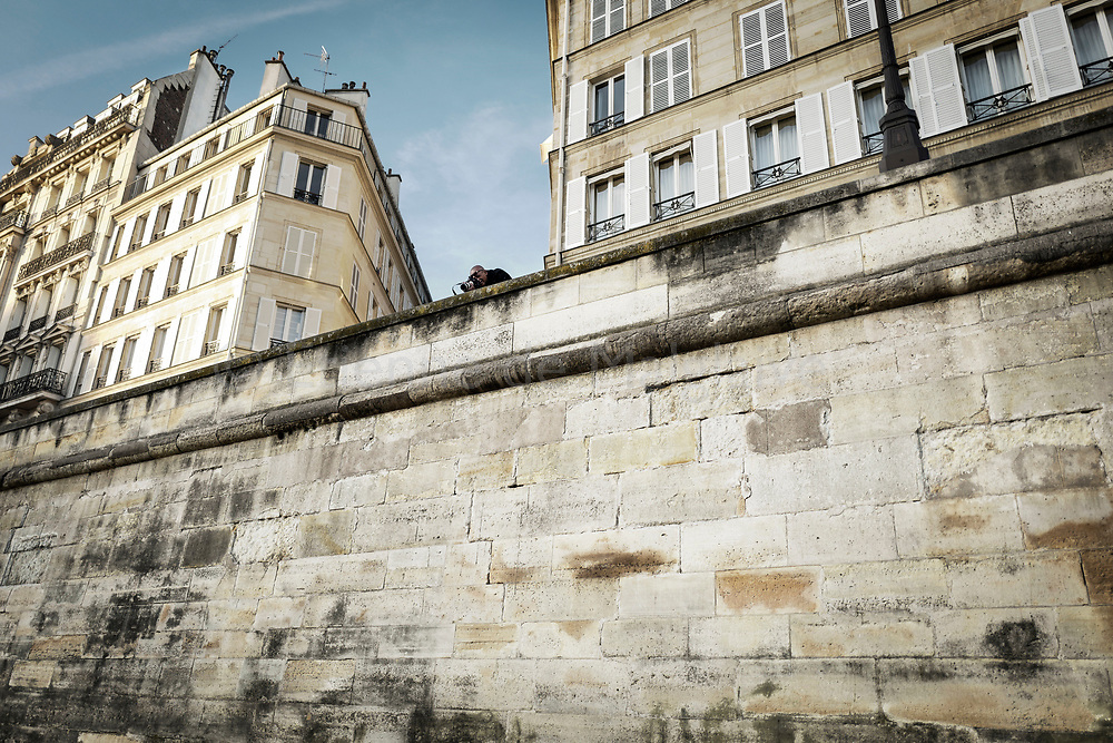 Scene of a sunny Sunday on Ile Saint Louis in Paris. A photographer shoots his girlfriend from the street level. 21 May 2017.