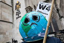 © Licensed to London News Pictures. 27/02/2020. London, UK. A man wearing a model of the earth on his head joins protesters who oppose the expansion of Heathrow Airport outside the High Court. Judges will deliver their ruling on a number of appeals against the planned construction of a third runway at the London airport. Photo credit: Rob Pinney/LNP