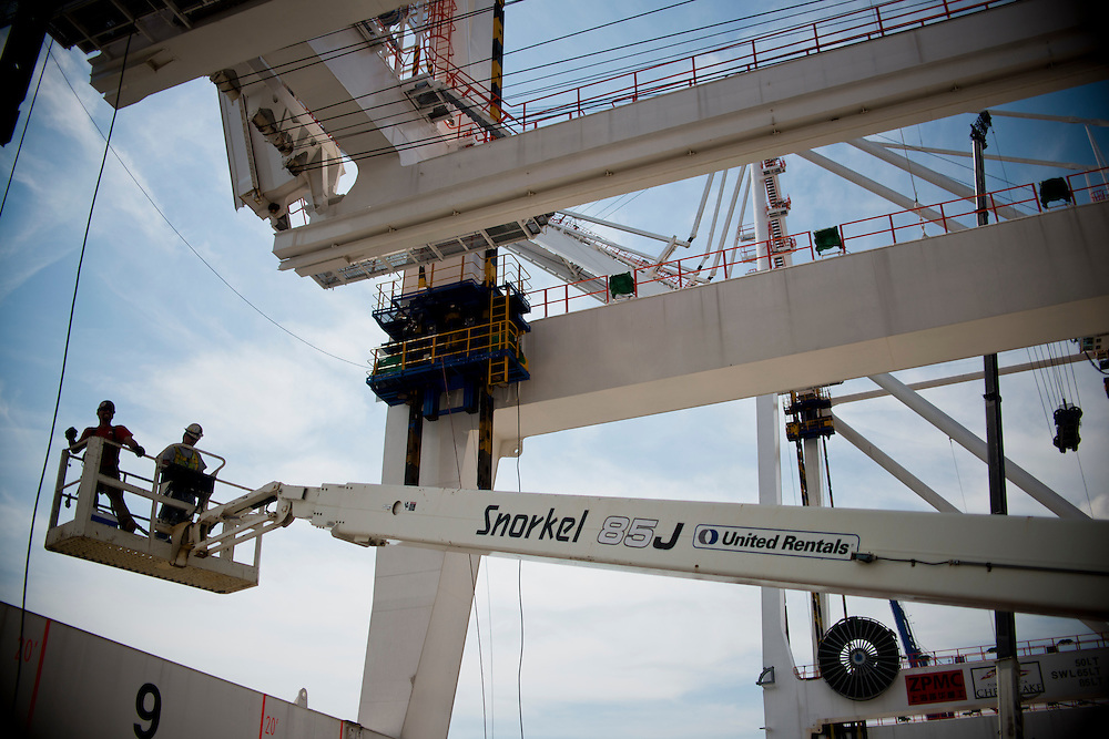 (photo by Matt Roth).Wednesday, July 11, 2012.Assignment ID: 30128574A..Jimmy Orr, left, and Ed Staylor, Jr., ride down a JLG Lift from atop the second of four super-post Panamax cranes to be erected at The Port of Baltimore's Seagirt Marine Terminal Wednesday, July 11, 2012. ..Once the building, testing and training is finished, the Seagirt terminal will join Norfolk, VA as one of the only two ports on the East Coast which can unload new Panamax sized container ships. The cranes are expected to be fully operational in September of this year.