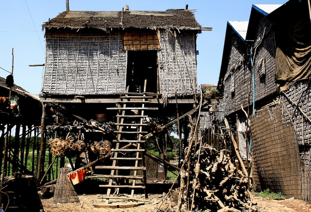 Front view of a small stilt house, showing access ladder and clusters of tools and equipment hanging in the shade underneath.  The woven straw matting wall of a larger house next door is shown.
