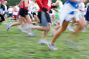 runners in a group at the start of a cross country race blurred showing motion as they run