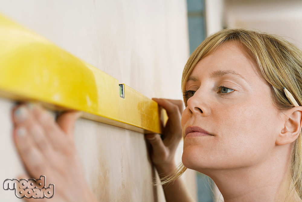 Woman using spirit level close-up