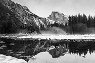 Half Dome in winter with reflections in Yosemite National Park, California.  black and white,