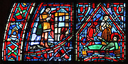 Geoffroy viscount of Chateaudun setting fire to the church's possessions (left) and Fulbert on his deathbed with his follower Berenger and a devil representing heresy (right), from the Life of Fulbert stained glass window, in the south transept of Chartres Cathedral, Eure-et-Loir, France. This window replaces the original 13th century window depicting the Life of St Blaise, which was destroyed in 1791. It was created in 1954 by Francois Lorin as a gift of the Institute of American Architects, on a theme chosen by the Canon Yves Delaporte. It depicts the life of Fulbert, bishop of Chartres in the 11th century. Chartres cathedral was built 1194-1250 and is a fine example of Gothic architecture. Most of its windows date from 1205-40 although a few earlier 12th century examples are also intact. It was declared a UNESCO World Heritage Site in 1979. Picture by Manuel Cohen