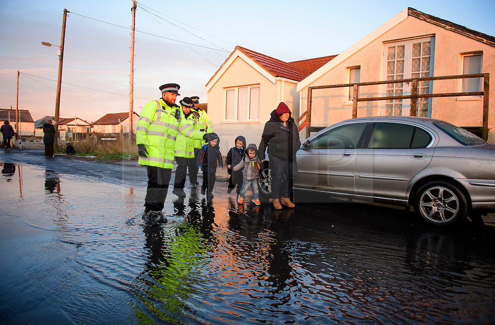 © Licensed to London News Pictures. 13/01/2017. Jaywick, UK. A police officer accompanies a woman and her y9oung children along the seafront at Jaywick, Essex, where homes were expected to evacuated due to the threat of flooding in low-lying areas . Photo credit: Ben Cawthra/LNP