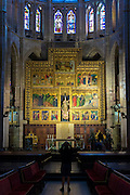 Tourist photographing altar and stained glass window in Cathedral de Santa Maria de Leon in Leon, Castilla y Leon, Spain