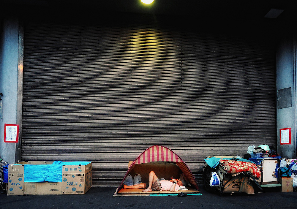 A homeless man hoping to secure dat labor work makes camp outside the Nishinari Labor Welfare Center in the Kamagasaki district of Osaka, Japan.