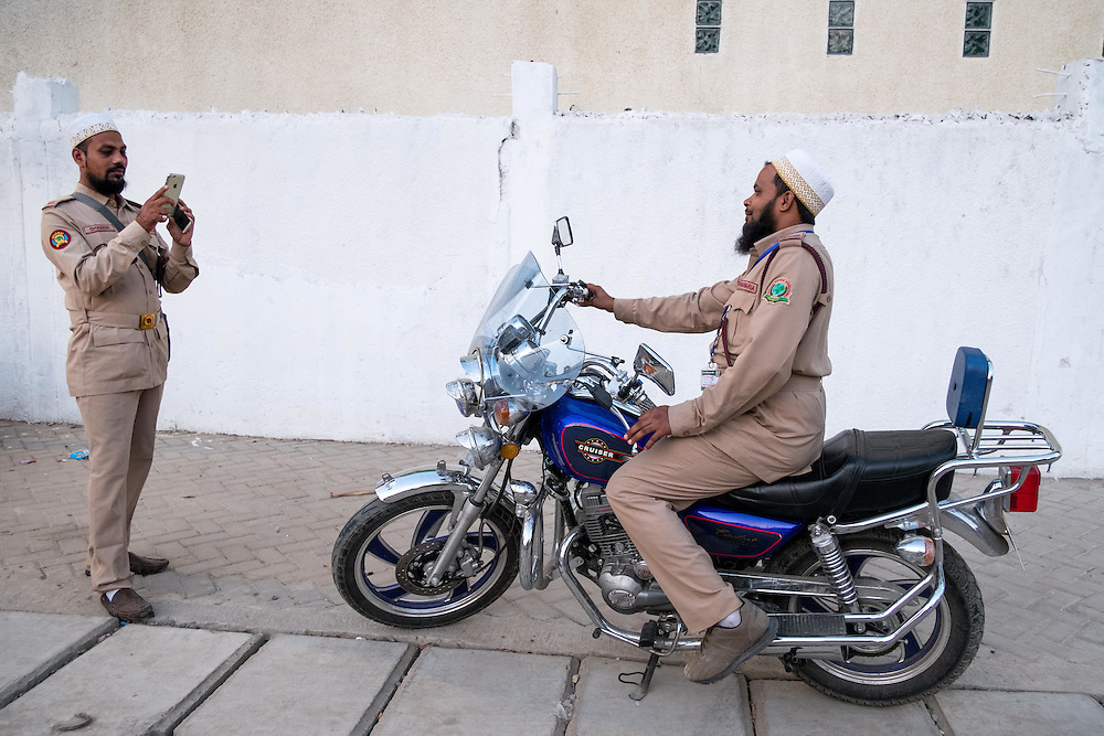 Dar es Salaam, Tanzania - 10/3/16 -  Dawoodi Bohra security guards from India pose for photographs on a motorcycle in Dar es Salaam on October 3, 2016.  Upwards of 30,000 members of the Dawoodi Bohra community have come to Dar as part of Ashara Mubaraka, commemorating the death of Hussein, the grandson of Muhammad. Members of the community -- this year, 44 nationalities are represented here in Dar -- gather in a different location every year along with their spiritual leader, His Holiness Dr. Syedna Mufaddal Saifuddin Saheb.  Photo by Daniel Hayduk