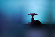 Selective focus on a mains metallic valve with blue background