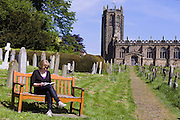 A tourist is reading on a bench inside the old century standing next to St Michaels' Church, in Coxwold, Yorkshire, England, United Kingdom.