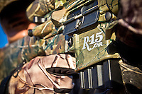 DETAILS OF A HUNTER WITH A REMINGTON R=15 RIFLE REALTREE AP CAMO