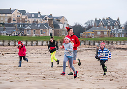 Pictured: Santa Beach Run on the scenic East Lothian coast. This new event is aimed at athletes, casual runners and families. It is hosted by Project Trust with proceeds enabling local school leavers to spend a year volunteering in India/Honduras to teach at a school with few teaching materials. Children return on the last leg of their 2km race. across the beach. 15 December 2018  <br /> <br /> Sally Anderson | EdinburghElitemedia.co.uk