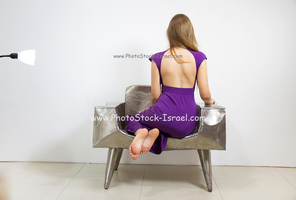 An attractive brunette woman sits with folded legs on a chair facing away from the camera wearing a purple backless evening dress