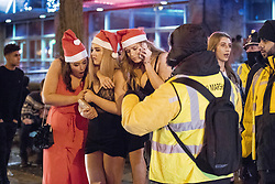 "© Licensed to London News Pictures . 16/12/2017. Manchester, UK. Three women dressed as Santa Claus huddle together for warmth as they wait for a taxi at Deansgate Locks . Revellers out in Manchester City Centre overnight during "" Mad Friday "" , named for historically being one of the busiest nights of the year for the emergency services in the UK . Photo credit: Joel Goodman/LNP"