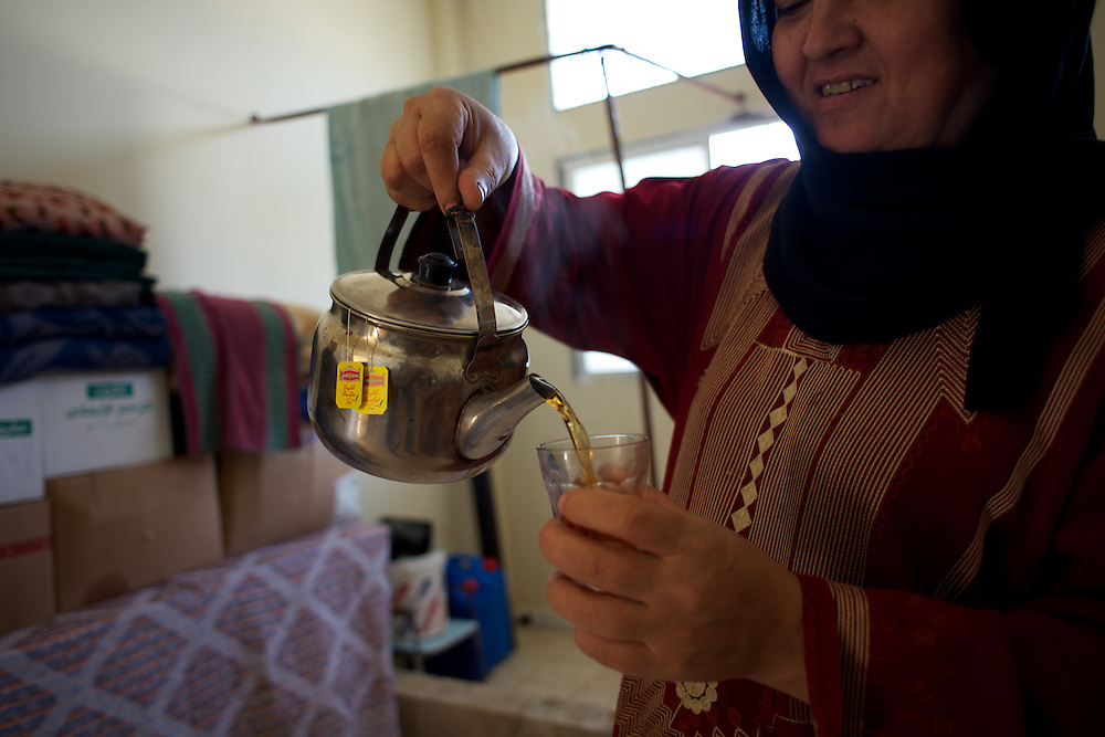 A Syrian refugee prepares some tea in a improvised room he shares with her family at a refugee center in Wadi Khaled, Lebanon.