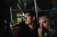 """ROME, ITALY - 27 JUNE 2017: (L-R) Director Fabio Cherstich and sets, video and costumes designer Gianluigi Toccafondo watch the final moments of the  """"Don Giovanni OperaCamion"""", an open-air opera performed on a truck in San Basilio, a suburb in Rome, Italy, on June 27th 2017.<br /> <br /> Director Fabio Cherstich's idae of an """"opera truck"""" was conceived as a way of bringing the musical theatre to a new, mixed, non elitist public, and have it perceived as a moment of cultural sharing, intelligent entertainment and no longer as an inaccessible and costly event. The truck becomes a stage that goes from square to square with its orchestra and its company of singers in Rome. <br /> <br /> """"Don Giovanni Opera Camion"""", after """"Don Giovanni"""" by Wolfgang Amadeus Mozart is a new production by the Teatro dell'Opera di Roma, conceived and directed by Fabio Cherstich. Set, videos and costumes by Gianluigi Toccafondo. The Youth Orchestra of the Teatro dell'Opera di Roma is conducted by Carlo Donadio."""