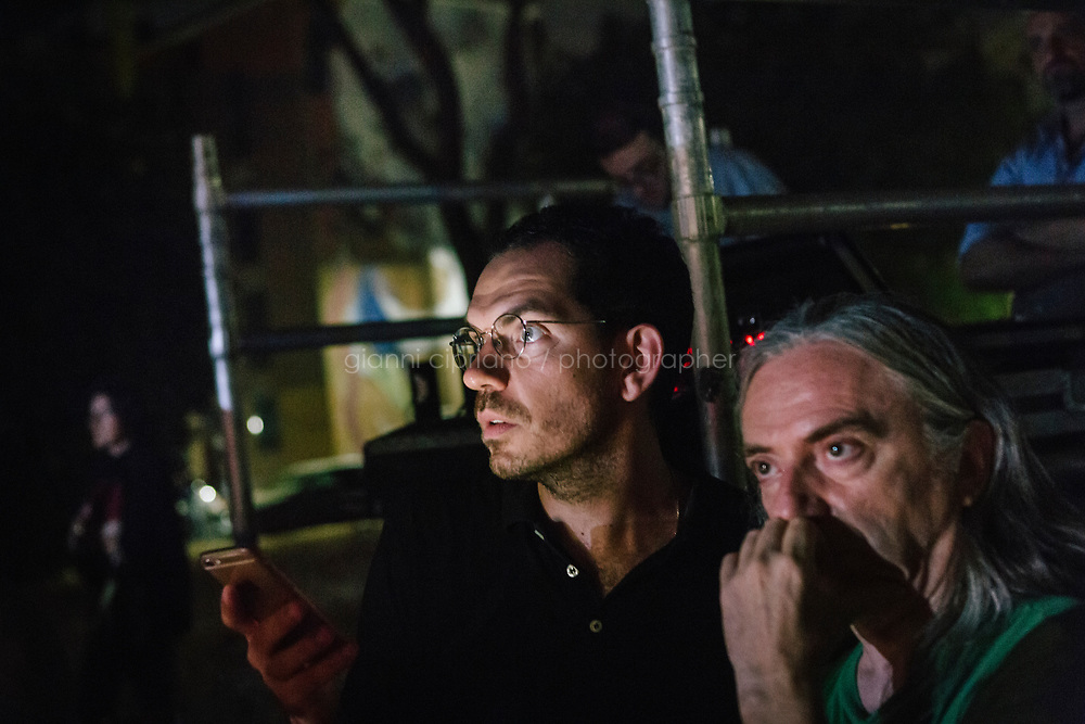 ROME, ITALY - 27 JUNE 2017: (L-R) Director Fabio Cherstich and sets, video and costumes designer Gianluigi Toccafondo watch the final moments of the  &quot;Don Giovanni OperaCamion&quot;, an open-air opera performed on a truck in San Basilio, a suburb in Rome, Italy, on June 27th 2017.<br /> <br /> Director Fabio Cherstich&rsquo;s idae of an &ldquo;opera truck&rdquo; was conceived as a way of bringing the musical theatre to a new, mixed, non elitist public, and have it perceived as a moment of cultural sharing, intelligent entertainment and no longer as an inaccessible and costly event. The truck becomes a stage that goes from square to square with its orchestra and its company of singers in Rome. <br /> <br /> &ldquo;Don Giovanni Opera Camion&rdquo;, after &ldquo;Don Giovanni&rdquo; by Wolfgang Amadeus Mozart is a new production by the Teatro dell&rsquo;Opera di Roma, conceived and directed by Fabio Cherstich. Set, videos and costumes by Gianluigi Toccafondo. The Youth Orchestra of the Teatro dell&rsquo;Opera di Roma is conducted by Carlo Donadio.