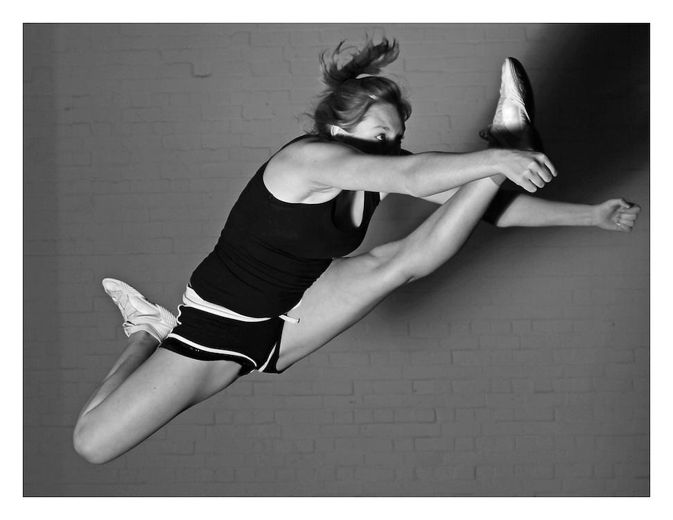 left leg cheerleading herky jump in black and white