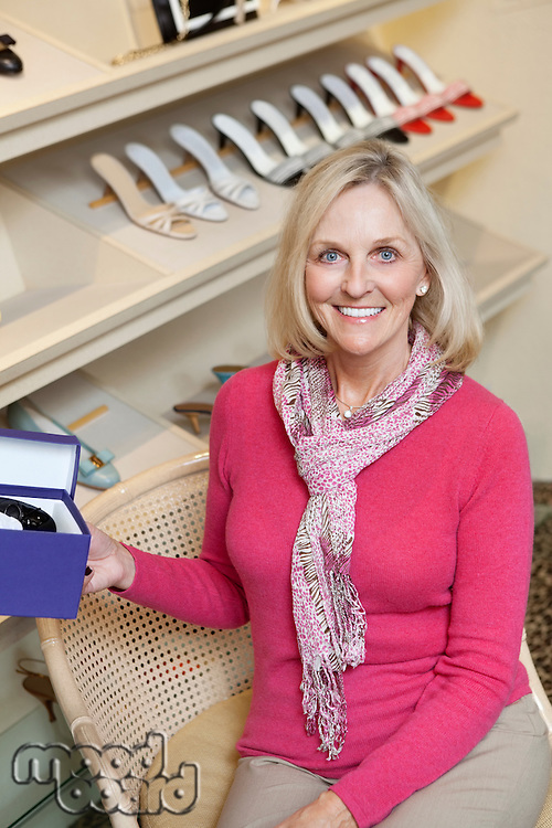 Portrait of a happy mature woman with shoe box in footwear store