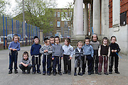 Orthodox Jewish school boys from the Bobov school watching the Lag B'Omer bonfire in the school playground. Lag B'Omer is the holiday celebrating the thirty-third day of the (counting of the) Omer. Jews celebrate it as the day when the plague that killed 24,000 people ended in the holy land (according to the Babylonian Talmud). Other sources say the plague was actually the Roman occupation and the 24,000 people died in the second Jewish - Roman war  (Bar Kokhba revolt of the first century).  Bonfires (used as signals in wartime) are symbolically lit to commemorate the holiday of Lag'B'Omer.