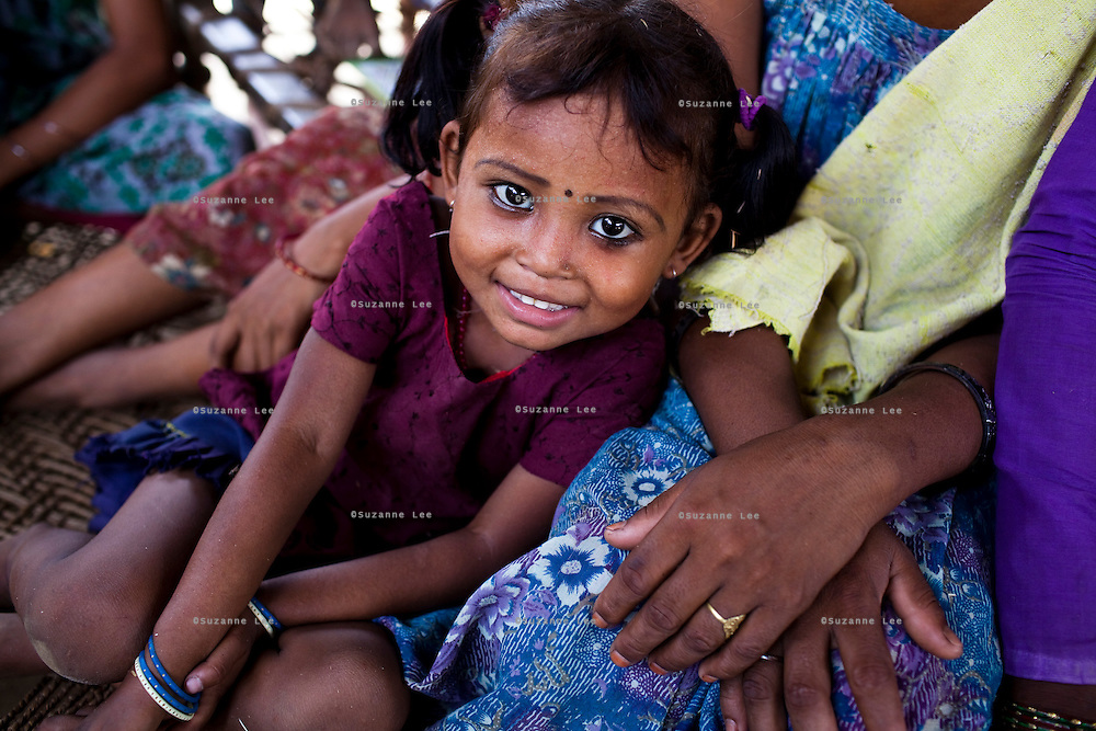 A young girl smiles at the camera as a group of teenaged mothers and child brides gather to listen to a female community health worker speak of family planning and pregnancy health in Bhaishahi village, Bardia, Western Nepal, on 29th June 2012. In Nepal, some girls not much older than this girl is married off as dowry payments for young girls are much less than older ones. In Bardia, StC works with the district health office to build the capacity of female community health workers who are on the frontline of health service provision like ante-natal and post-natal care, and working together against child marriage and teenage pregnancy especially in rural areas. Photo by Suzanne Lee for Save The Children UK