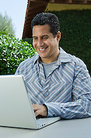 Man using laptop in back yard