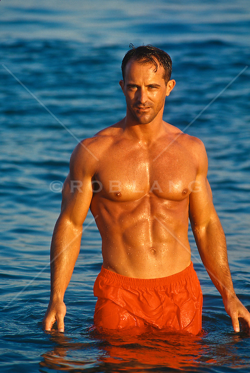 Man in red shorts standing in the ocean