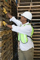 Man inspecting wooden pallets in distribution warehouse