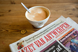 Detail of coffee and local newspaper in traditional bakers shop and cafe in central Antwerp in Belgium