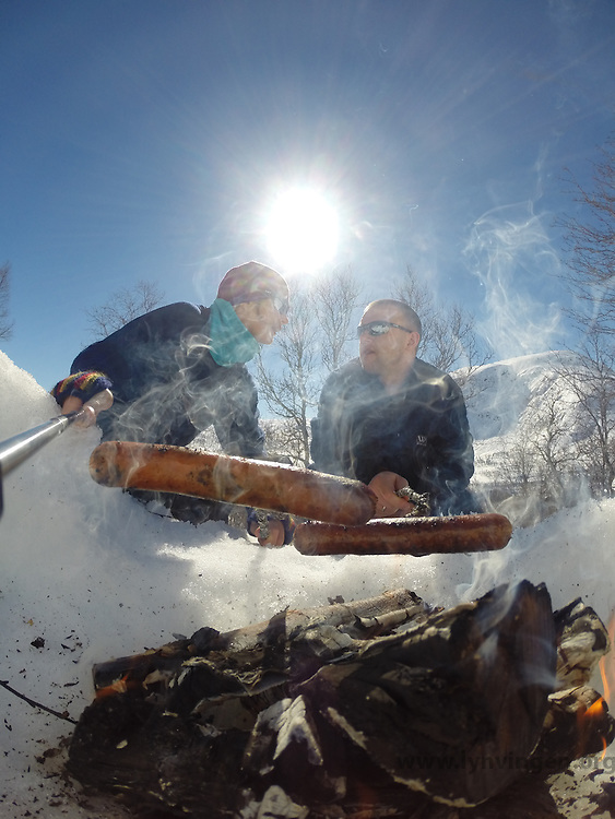 Man and woman grilling sausage on bonfire