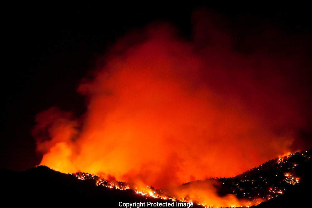 As night falls, on the Dean Peak wildfire, gusty dry winds spread the flames through the Hualapai mountains of Arizona.