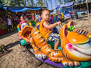 28 OCTOBER 2012 - SAI BURI, PATTANI, THAILAND:   A child on a ride at a carnival on the beach in Sai Buri. Sai Buri, in Narathiwat province, Thailand, has been the scene of several bloody attacks in Thailand's long running Muslin insurgency. In September, 2012, a large car bomb was detonated in front of a Buddhist owned business in the village killing six and injuring scores of people. In October, 2012, in a possible revenge attack, hand grenades were rolled into a crowd of Muslim diners, injuring 16. More than 5,000 people have been killed and over 9,000 hurt in more than 11,000 incidents, or about 3.5 a day, in Thailand's three southernmost provinces and four districts of Songkhla since the insurgent violence erupted in January 2004, according to Deep South Watch, an independent research organization that monitors violence in Thailand's deep south region that borders Malaysia.  PHOTO BY JACK KURTZ