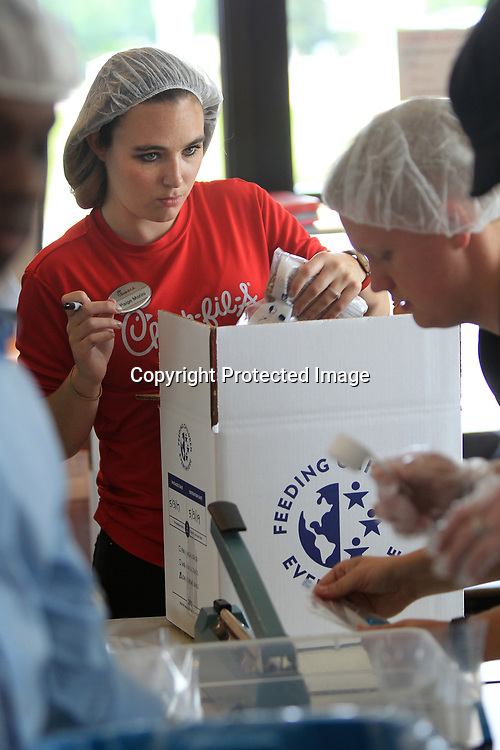 Page Morini a Chick-fil-a team member from Atlanta, boxes up meals for the St. Luke Food Pantry Wednesday. The restaurant worked to fill 10,000 meals for the pantry inside the store.