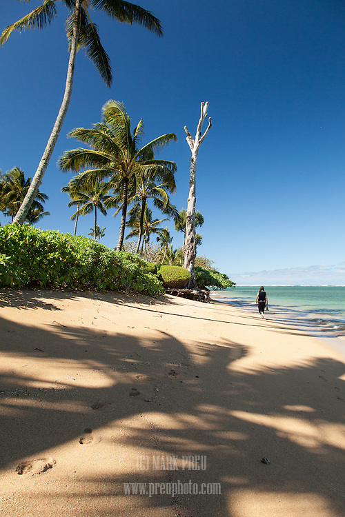 A lone walker on Anini Beach on the north shore of Kauai.