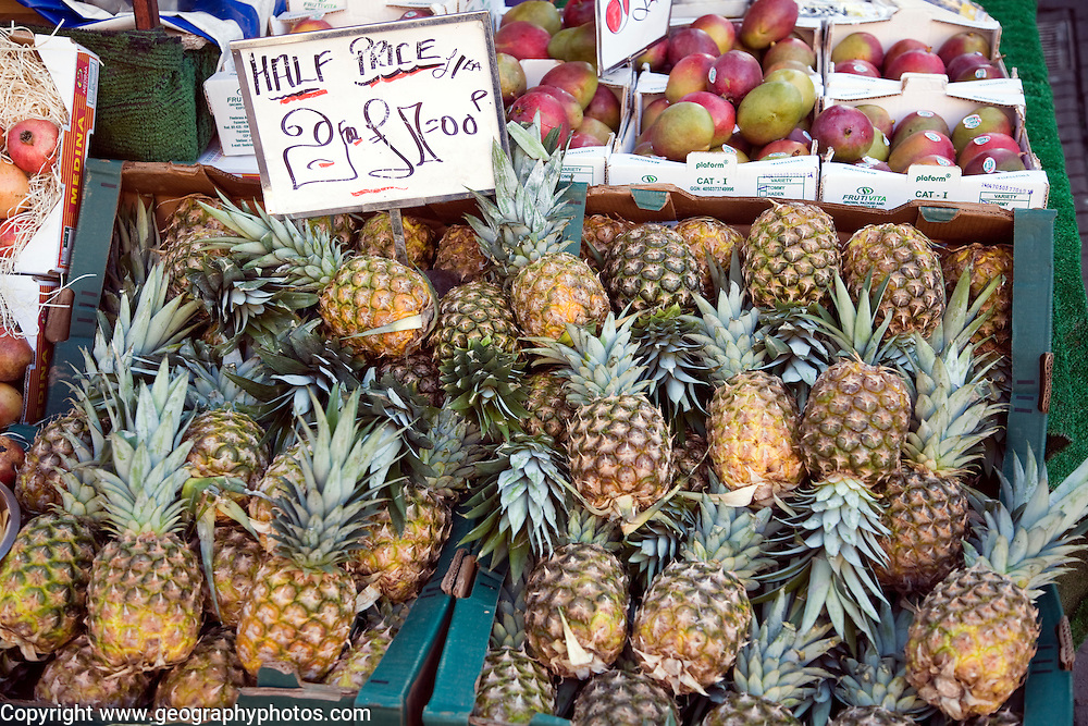 Half price pineapples for sale on market stall priced two for £1.00