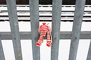 A child's lost toy has been left on railway railings during wintry snow at Herne Hill, south London.