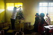 CLIENT: PROJECT HOPE<br /> <br /> Seventh grade students watch as their teacher places a star atop their classroom Christmas tree at storm-damaged Candalaria National High School, which was being used as a medical clinic site in the wake of Typhoon Haiyan, in the village of Roxas Ocho, Philippines.