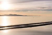 The sunrise over the low tide sandbar at Cordova Bay in Victoria, BC glows gold.