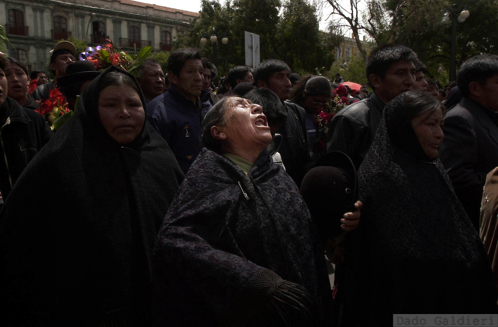 Indigenous Bolivian women cry as they walk in a funeral procession in honor of nine police officers who were killed in clashes last Wednesday, in La Paz, Bolivia on Friday, Feb. 14, 2003. The violence in La Paz began Wednesday when 7,000 striking police officers and civilian protesters clashed with government troops over a new tax plan. The rampage left 22 people dead.(Dado Galdieri)