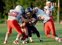 Trinitys Josh Hughes and Zack Poole clamp down on Merrimack Valley running back Justin Abbot during Friday Night Football in Concord.  (Karen Bobotas/for the Concord Monitor)