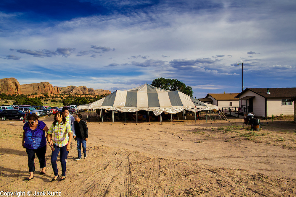 """12 JULY 2012 - FT DEFIANCE, AZ:  A family walks to the youth worship service, past the main tent, at the 23rd annual Navajo Nation Camp Meeting in Ft. Defiance, north of Window Rock, AZ, on the Navajo reservation. Preachers from across the Navajo Nation, and the western US, come to Navajo Nation Camp Meeting to preach an evangelical form of Christianity. Evangelical Christians make up a growing part of the reservation - there are now more than a hundred camp meetings and tent revivals on the reservation every year. The camp meeting in Ft. Defiance draws nearly 200 people each night of its six day run. Many of the attendees convert to evangelical Christianity from traditional Navajo beliefs, Catholicism or Mormonism. """"Camp meetings"""" are a form of Protestant Christian religious services originating in Britain and once common in rural parts of the United States. People would travel a great distance to a particular site to camp out, listen to itinerant preachers, and pray. This suited the rural life, before cars and highways were common, because rural areas often lacked traditional churches.    PHOTO BY JACK KURTZ"""