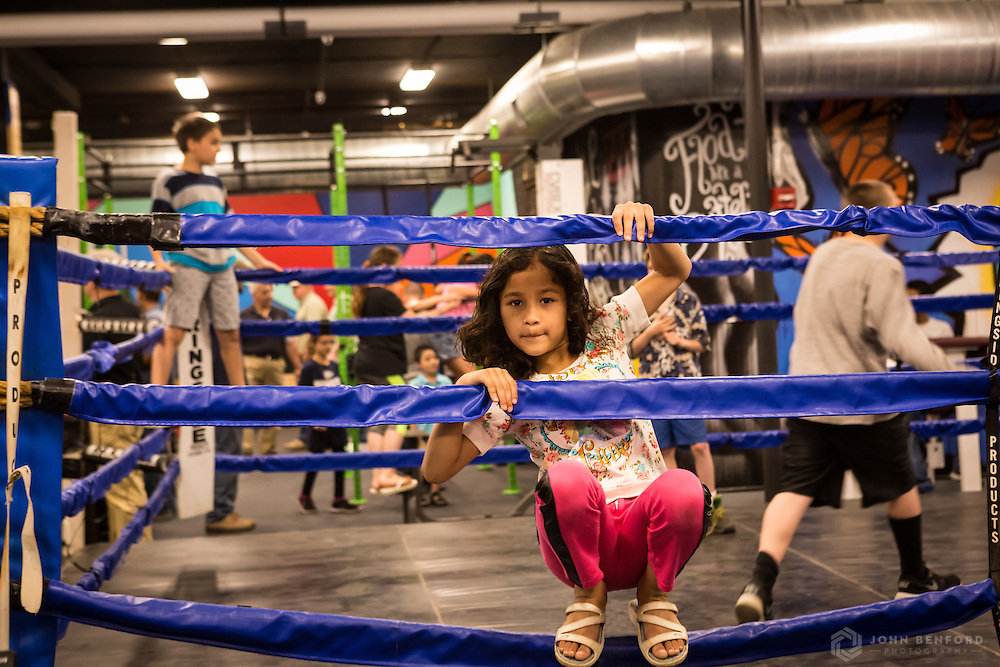 A child peers through the ropes in the renovated boxing ring during the the reveal event for the 2016 Building on Hope project at the Michael Briggs Community Center / Manchester Police Athletic League in Manchester, NH.