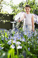 Portrait of young girl (5-6) playing in garden wearing fairy costume