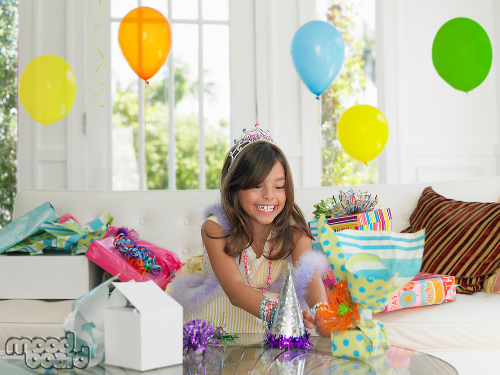 Young girl (7-9) opening birthday presents smiling