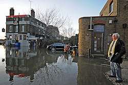 04/03/2010 River Thames breaks its banks in Richmond, London. The white cross pub is cut off and locals watch as an enterprising local brings a boat over to ferry them across. The pubs normal 'high tide' entrance was only reachable by boat.